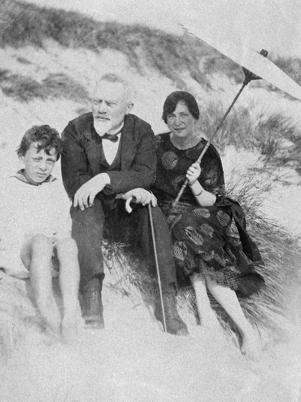 Jens Michael Andersen på strand med søn og hustru med parasol