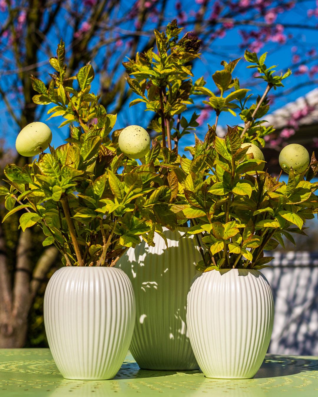 Hvide vaser fra Michael Andersen med grene og påskeæg på lysegrønt havebord foran tepavillon og ferskenblomsttræ