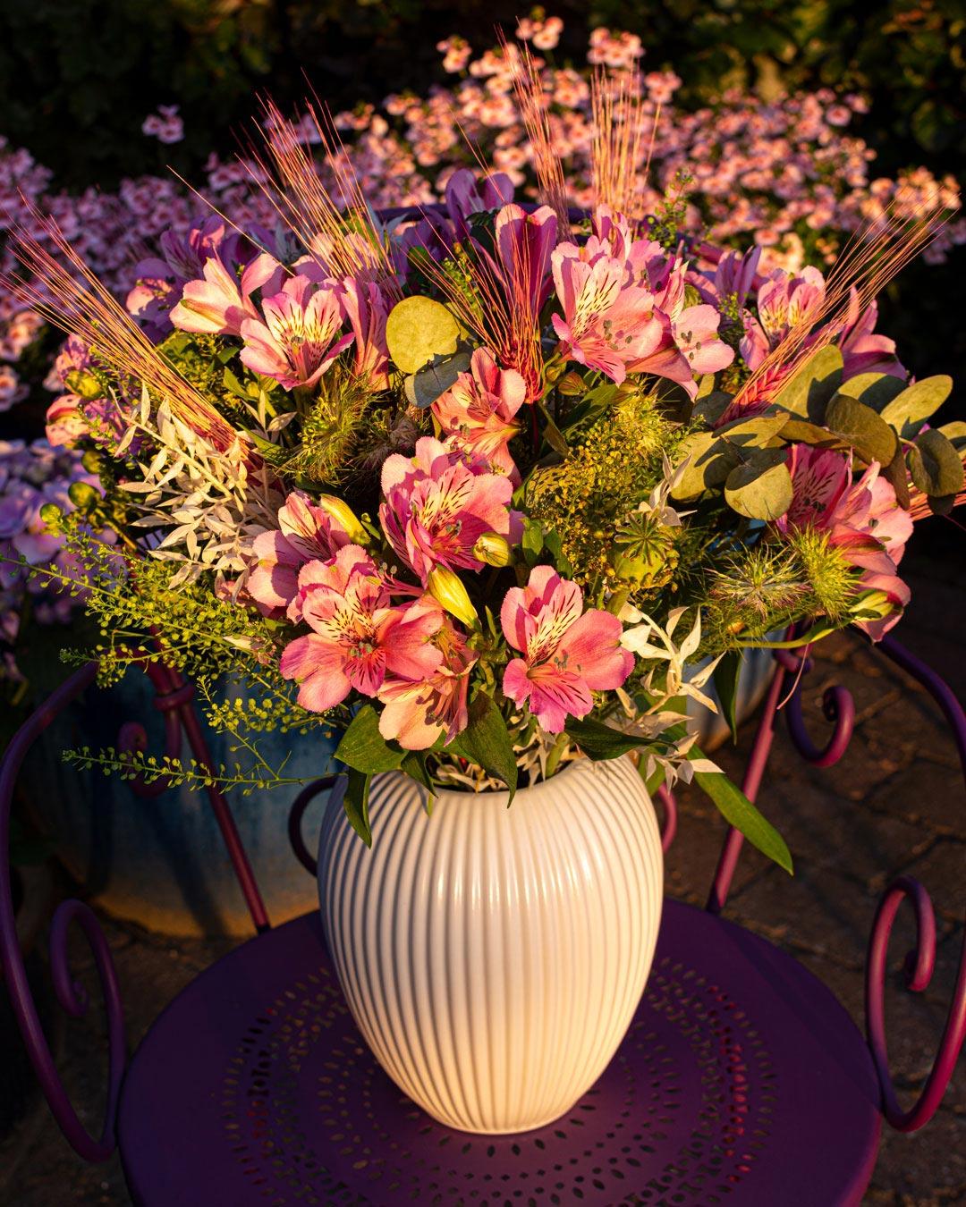 Hvid vase fra Michael Andersen Keramik Model 4767 23 cm med pink liljer på lilla Fermob 1900 stol i have med aftensol