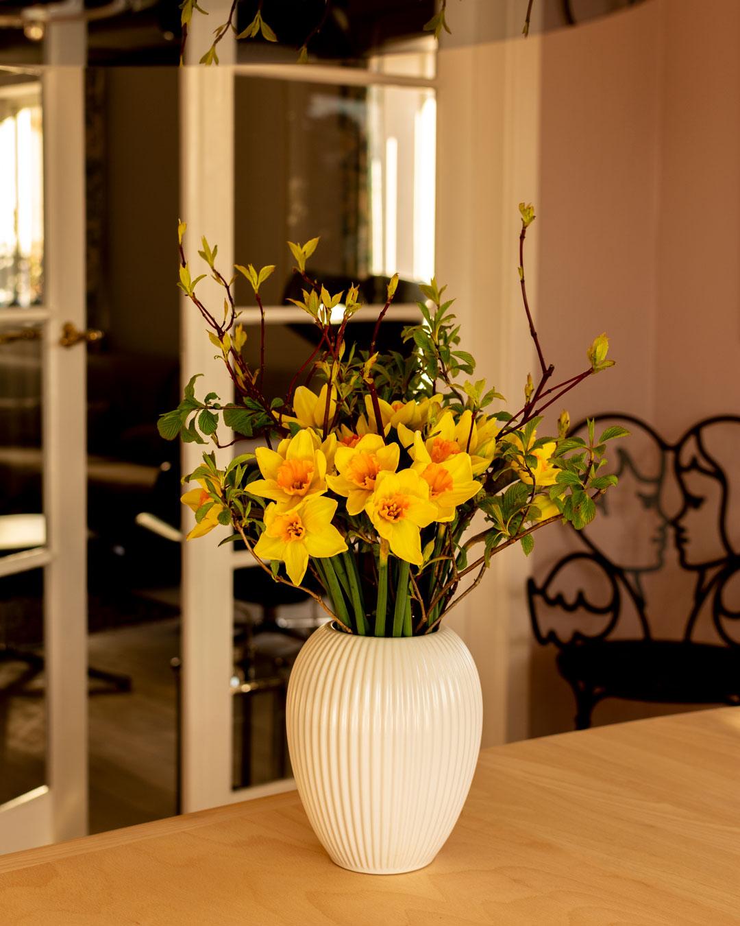 Hvid vase fra Michael Andersen Keramik med påskeliljer og grene fra haven på spisestuebord