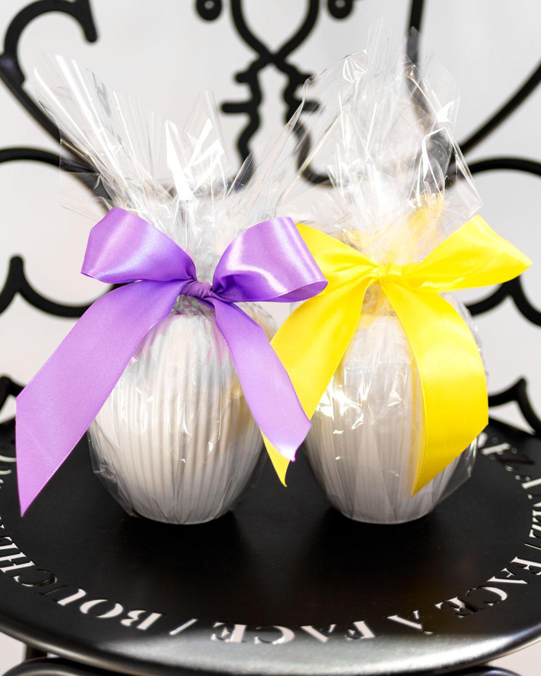 To små hvide vaser fra Michael Andersen Keramik Model 4767 pakket ind i cellofan som påskeæg med lille og gul sløjfe på sort englestol