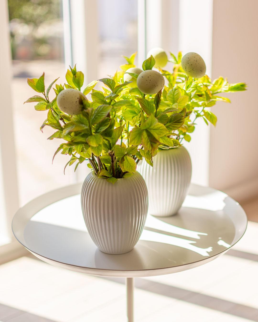 To små hvide vaser fra Michael Andersen Keramik Model 4767 med grene og påskeæg på lille hvidt bord