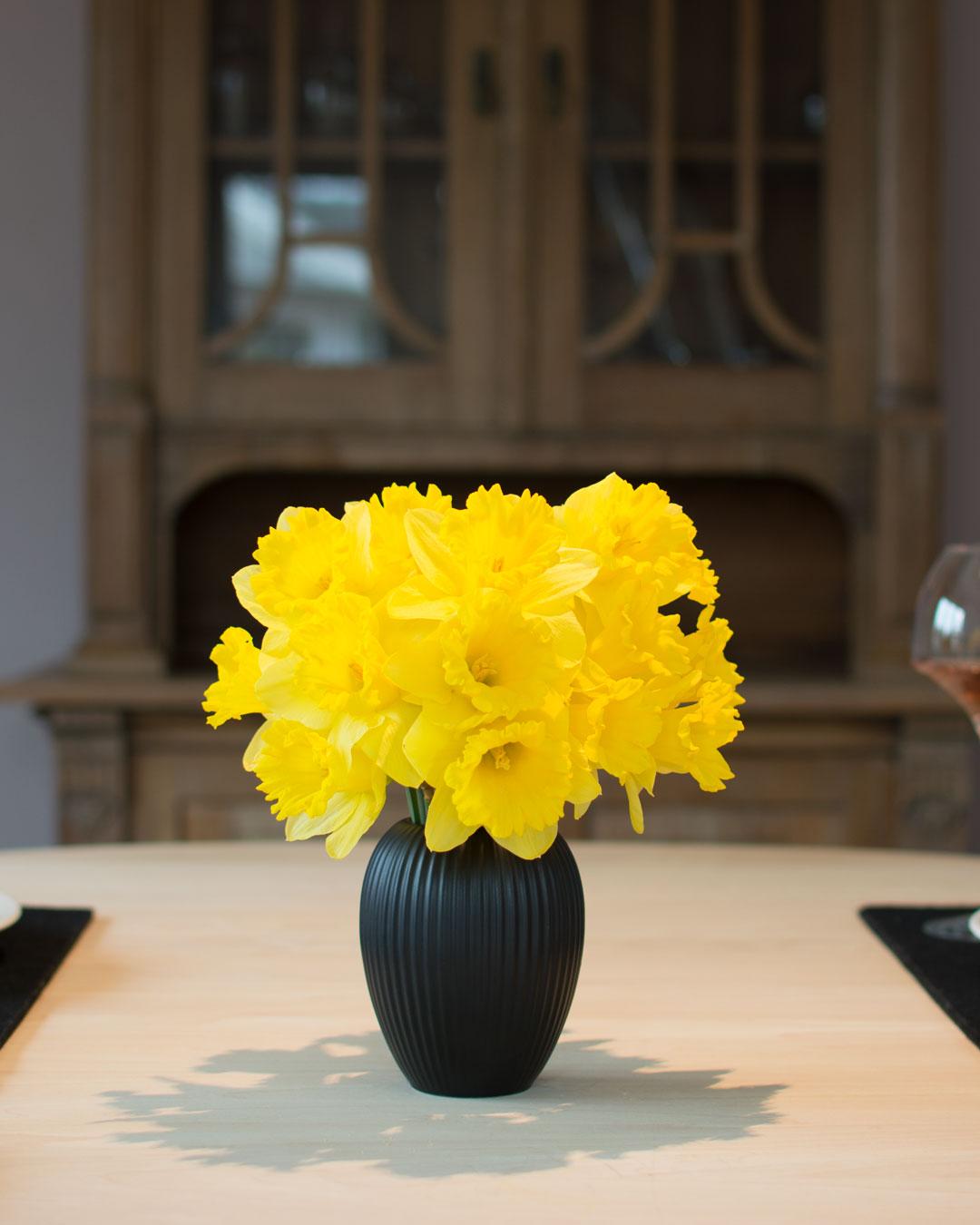 Sort vase fra Michael Andersen Keramik Model 4767 i 12 cm med påskeliljer på spisebord