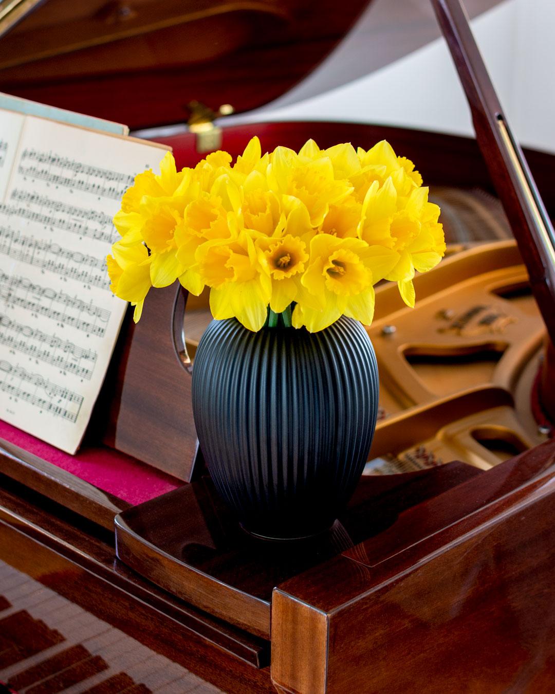 Sort vase fra Michael Andersen Keramik med påskeliljer på flugel af mørk træsort